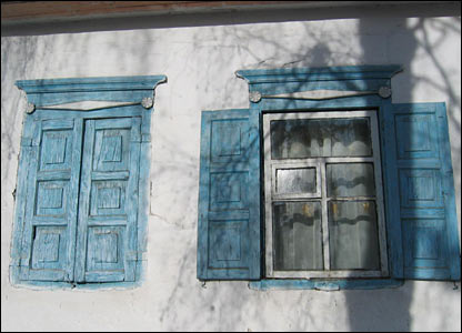 Two sets of blue shutters on an old house