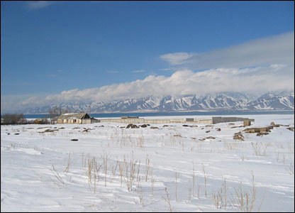 A snow-covered field near Karakol, with mountains in the background.