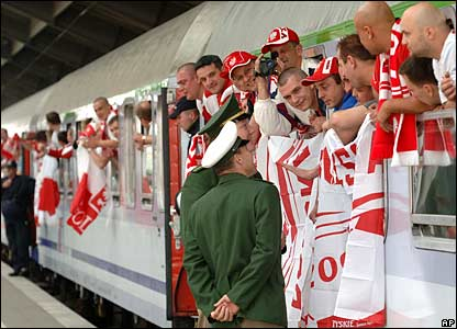 Polish fans on board a train talk to police officers on the platform