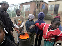 Soweto residents warm up over a fire in the street