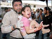 An injured Palestinian girl is being carried into the hospital in the northern Gaza Strip town of Beit Lahiya