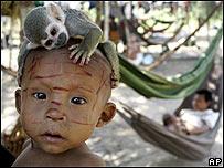 Ni�o de la comunidad Nukak-Maku juega con un mono en Agua Bonita, Colombia.