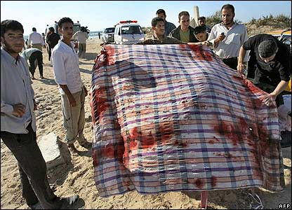 Palestinians display a bloodstained sheet on the beach