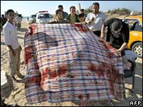 Palestinians recover a blood-stained table cloth from the bombed beach in Gaza