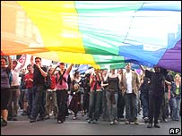 People at the rally holding the rainbow flag