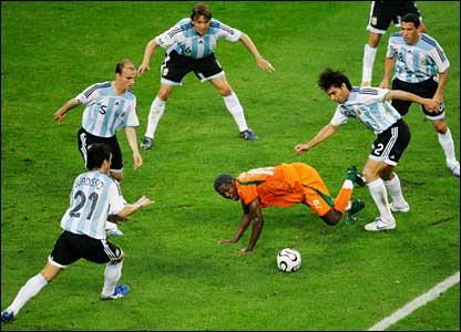 Kader Keita goes to ground surrounded by Argentina players