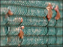 Inmates hold on to a fence at the US base in Guantanamo Bay, Cuba
