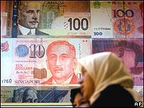 Mujer frente a cartel con billetes de distintos pa�ses en Malasia.