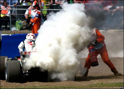 Jenson Button's flaming Honda is put out by a marshall