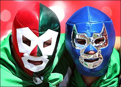 Two masked Mexico fans await their game against Iran