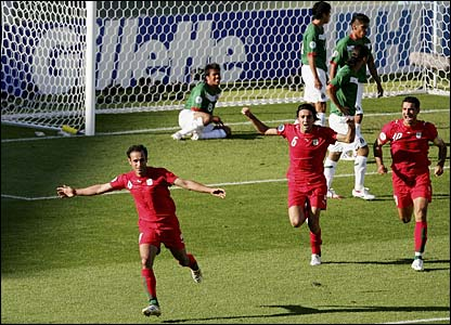 Mexico's defenders look dejected as Yahya Golmohammadi celebrates his goal
