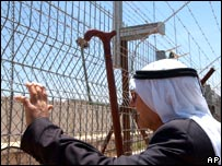 Palestinian stands at an Israeli border fence