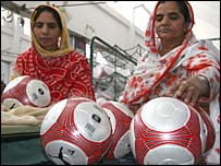 Women in assembly line cleaning footballs