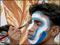 A young Indian fan gets a dab of paint