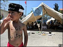 "Palestinian boy with the words ""I'm hungry"" in a protest against the cutting of aid"
