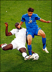 Italy's Simone Perrotta (right) is tackled by Sulley Muntari