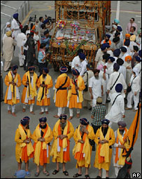 Indian Sikh pilgrims surround a van carrying a palanquin with their holy book as they enter Pakistan near Lahore