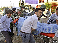 A civilian wounded in a car bombing in Kirkuk is rushed to an ambulance