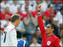 Peter Crouch is booked by referee Marco Rodriguez