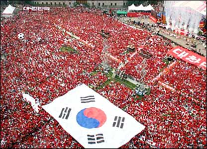South Korean fans carry a huge national flag as they gather to watch the match outside the Seoul City Hall in South Korea