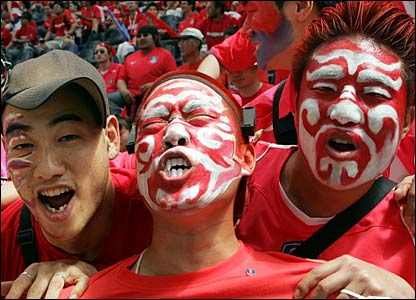 Three supporters of South Korea cheer prior to the Group G match