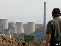 A Chinese man walks past a power plant in Hebei province, north of Beijing