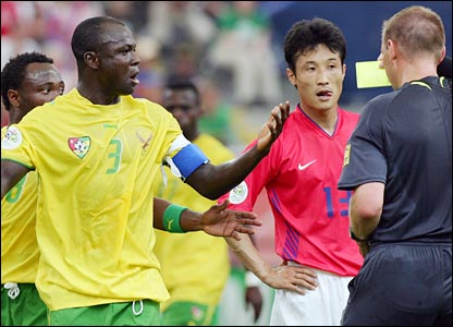 British referee Graham Poll gives a yellow card to Togolese defender Jean-Paul Abalo (l) as South Korean midfielder Eul Yong Lee looks on
