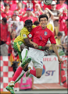 Togolese forward Emmanuel Adebayor vies with South Korean defender Jin Cheul Choi