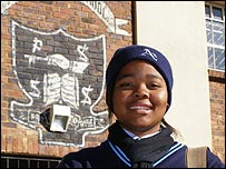 Pupil standing in front of Phefeni Secondary School in Soweto