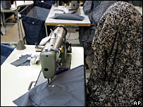A heavily-veiled woman sits at her sewing machine