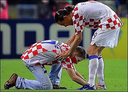 A Croatia fan bows down at the feet of striker Dado Prso