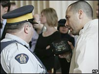 Adil Charkaoui (right) shows a police officer his court ordered GPS tracking device before going through security at the Supreme Court of Canada
