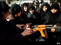 Veiled Iraqi women looking at an AK 47 assault rifle