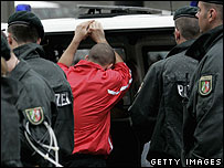 A Poland fan is stopped by police in Dortmund