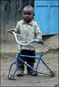 Boy with broken bicycle in Nairobi's Kibera slum