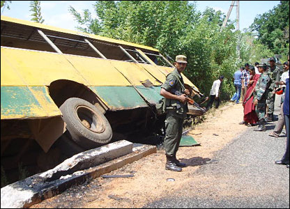 Soldiers patrol near a bus overturned by a landmine blast in Kabithigollewa northeast of Colombo