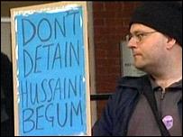 "Man holding ""Don't detain Hussaini Begum"" placard"