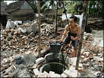 A man draws water from a well in Palbapang on 6 June 2006
