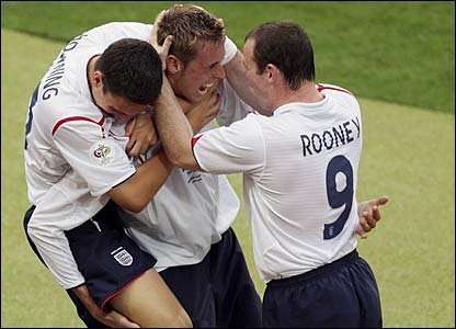 Peter Crouch is congratulated by Stewart Downing and Wayne Rooney
