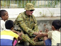 An Australian peacekeeper talks to local children