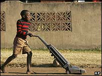 Boy playing with an old hoover in Soweto street