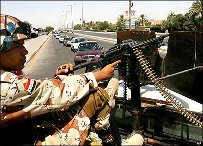 Soldier halts traffic at checkpoint in Baghdad