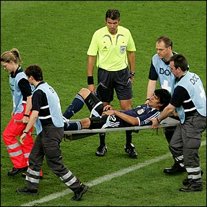 Luis Gonzalez is carried off on a stretcher under the watchful eye of referee Roberto Rosetti