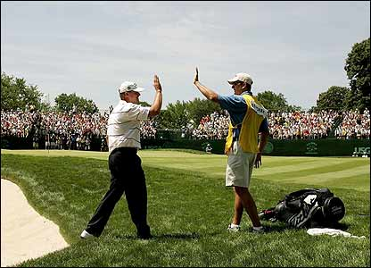 Stricker celebrates with his caddy after holing from the bunker