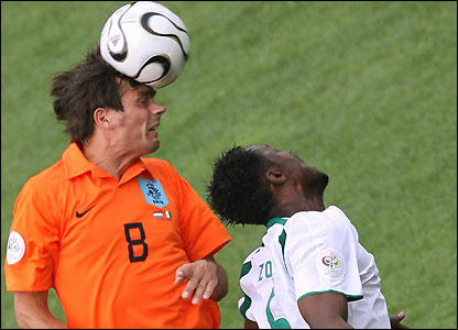 Phillip Cocu of Holland beats Didier Zokora in the air to
