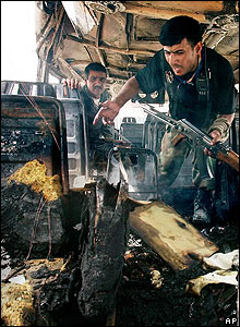 Iraqi soldiers inspect bombed minibus