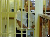 A prison guard locks a door