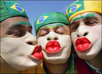 Three Brazil fans pose as they wear masks with big red lips