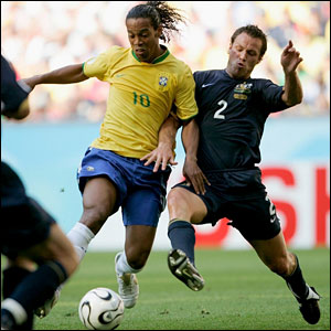 Ronaldinho is tackled from behind by Lucas Neill