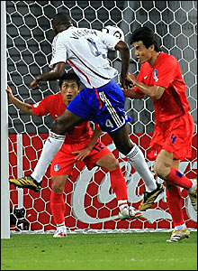 Patrick Vieira (centre) heads Zinedine Zidane's corner goalwards, but South Korea goalkeeper Lee Woon-Jae claws the ball away